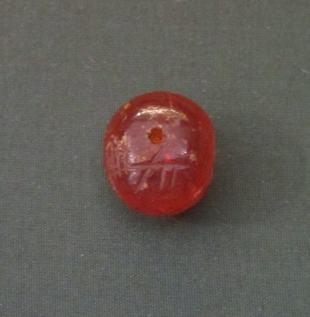 """Fig. 3: Ogham inscription on amber bead. Identified as ᚐᚈᚒᚉᚋᚂᚒ """"ATUCMLU"""" (only ... ᚋᚂ """"ML"""" is visible on image). Ireland, 5th-7th century, British Museum. By BabelStone (Own work) [CC BY-SA 3.0 (http://creativecommons.org/licenses/by-sa/3.0)], via Wikimedia Commons"""